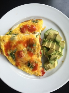 Breakfast frittata made of cherry tomatoes, spinach, and onion, topped with cheddar cheese and avocado on the side.